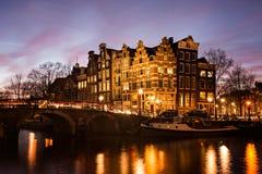Amsterdam kanalhus på skymning Arkivbild