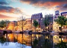 Amsterdam kanalhus på solnedgångreflexioner, Nederländerna arkivfoton