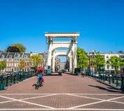 Amsterdam, le 7 mai 2018 - vélo de monte de personnes traversant la rivière AM image libre de droits