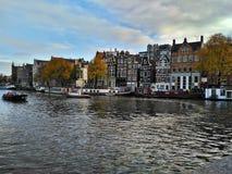 Amsterdam/los Países Bajos - 30 de octubre de 2016: Opinión sobre el canal de Amsterdam, los barcos y las casas holandesas tradic imagen de archivo libre de regalías