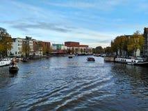 Amsterdam/los Países Bajos - 30 de octubre de 2016: Opinión sobre el canal de Amsterdam, teatro de la ópera central en la distanc fotografía de archivo