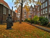 Amsterdam/los Países Bajos - 30 de octubre de 2016: Vieja yarda Begijnhof con las casas, el jardín y una escultura imagen de archivo