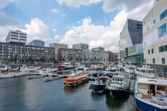 AMSTERDAM, los PAÍSES BAJOS - 3 de septiembre de 2017: El puerto con el lujo colorido envía en Amsterdam céntrica, delante del pa Imagenes de archivo