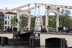 Amsterdam Magere Brug. AMSTERDAM, NETHERLANDS - JULY 8, 2017: People visit Magere Brug The Skinny Bridge in Amsterdam, Netherlands. Amsterdam is the capital city stock photos