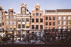 AMSTERDAM - MAJ 13: Cyklar som parkeras på en bro över kanalerna av Amsterdam Arkivbild