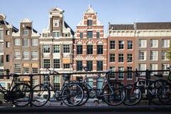 AMSTERDAM - MAJ 13: Cyklar som parkeras på en bro över kanalerna av Amsterdam Royaltyfri Foto