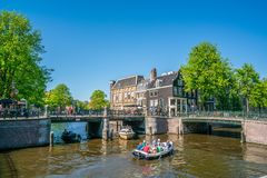 Amsterdam, May 7 2018 - The corner of Prinsengracht and Leidsegr. Acht with small boats sailing on the channels on a sunny day Royalty Free Stock Image
