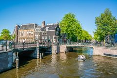 Amsterdam, May 7 2018 - The corner of Prinsengracht and Leidsegr. Acht with small boats sailing on the channels on a sunny day Royalty Free Stock Images