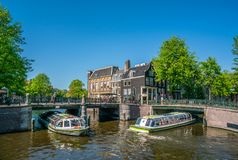 Amsterdam, May 7 2018 - The corner of Prinsengracht and Leidsegr. Acht with tourist boats sailing on the channels on a sunny day Stock Images