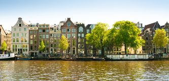 Amsterdam, May 7 2018 - view on the river Amstel filled with small boats and traditional houses in the background on a summer day stock image