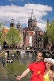 Amsterdam med folk som gör selfie i Holland Royaltyfria Bilder