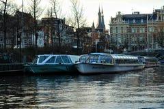 amsterdam morgon Vattengata med fartyg på pir, reflekterad i tyst vatten arkivbild