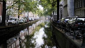 Amsterdam morning in center city - street with bicycles and cars on canal, Autumn, Netherlands. Wide angle stock footage