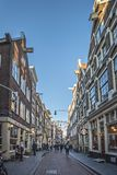 Amsterdam, narrow street, in the center. All day life with the shops people with shopping bags, bicycles, outdoor shopkeepers and Royalty Free Stock Images