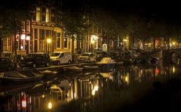 Amsterdam natt: kanal i rött område arkivbild