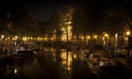 Amsterdam natt: ljus och kanal arkivbild