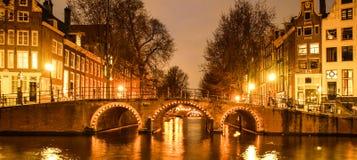 amsterdam natt Upplyst bro över vattenkanalen, gracht Nederländerna Arkivfoton