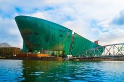 AMSTERDAM NEDERLÄNDERNA, APRIL, 23 2018: NEMO Science Museum byggnad är i form av ett grönt skepp, planlades förbi arkivfoton