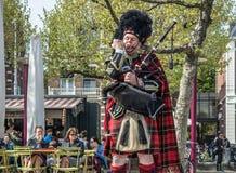 Amsterdam Nederländerna - April 31, 2017: Skotsk säckpipeblåsare som trimmar hans instrument i gatorna av Amsterdam att bära Arkivfoto