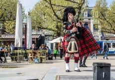 Amsterdam Nederländerna - April 31, 2017: Skotsk säckpipeblåsare som trimmar hans instrument i gatorna av Amsterdam att bära Arkivfoton