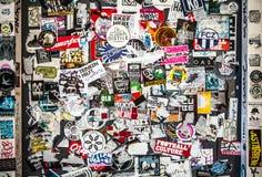 AMSTERDAM NEDERLÄNDERNA - AUGUSTI 15, 2016: Gataväggen täckte talrika mångfärgade klistermärkear på Augusti 15 i Amsterdam Arkivfoton