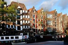 AMSTERDAM NEDERLÄNDERNA - 15. av APRIL 2014: Byggnader och fartyg i gatan av Amsterdam, Nederländerna Arkivbilder