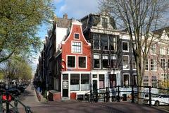AMSTERDAM NEDERLÄNDERNA - 15. av APRIL 2014: rött hus i gatan av Amsterdam, Nederländerna Arkivbilder