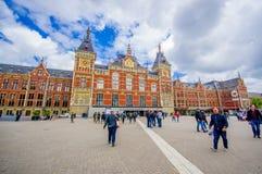 Amsterdam Nederländerna - Juli 10, 2015: Centralstation som den sedda utifrån plazaen, härlig traditionell europé Arkivbild