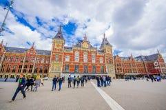Amsterdam Nederländerna - Juli 10, 2015: Centralstation som den sedda utifrån plazaen, härlig traditionell europé Arkivbilder