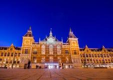 Amsterdam Nederländerna - Juli 10, 2015: Centralstation som den sedda utifrån plazaen, härlig traditionell europé Arkivfoton