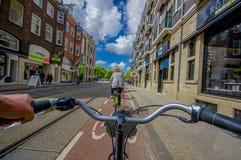 Amsterdam Nederländerna - Juli 10, 2015: Cyklistpunkt av sikten som cykla till och med stadsgator på en härlig sumerdag Royaltyfri Bild