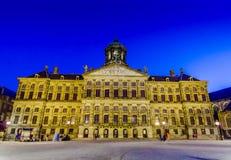 Amsterdam Nederländerna - Juli 10, 2015: Den oerhörda kungliga slotten som sett across från fördämningfyrkant i ett härligt Arkivfoton