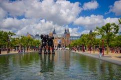 Amsterdam Nederländerna - Juli 10, 2015: Den stora vattenspringbrunnen lokaliserade framme av det nationella museet på ett härlig Royaltyfri Bild