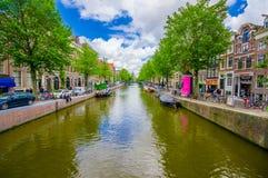 Amsterdam Nederländerna - Juli 10, 2015: En av många vattenkanaler som kör till och med staden, parkerade små fartyg Arkivbilder