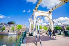 Amsterdam Nederländerna - Juli 10, 2015: Gammal metallbro med den härliga designen som sträcker över en av många vatten Arkivfoton