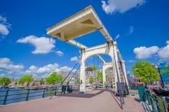 Amsterdam Nederländerna - Juli 10, 2015: Gammal metallbro med den härliga designen som sträcker över en av många vatten Arkivbilder
