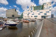 AMSTERDAM Nederländerna - JULI 03, 2016: Härbärgera med färgrika fartyg som är främsta av den moderna kontorsbyggnaden för domsto Arkivfoto
