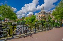 Amsterdam Nederländerna - Juli 10, 2015: Härlig strand för byggnadsfasadsammanträde, cyklar som framme parkeras på bron Arkivfoton