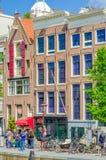 Amsterdam Nederländerna - Juli 10, 2015: Traditionella holländska stadskvarter med charmiga byggnader för röd tegelsten Fotografering för Bildbyråer