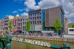 Amsterdam Nederländerna - Juli 10, 2015: Traditionella holländska stadskvarter med charmiga byggnader för röd tegelsten bredvid v Arkivbild