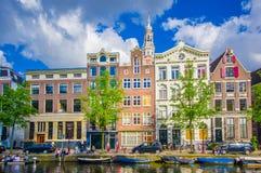 Amsterdam Nederländerna - Juli 10, 2015: Traditionella holländska stadskvarter med charmiga byggnader för röd tegelsten bredvid v Royaltyfri Bild