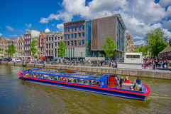 Amsterdam Nederländerna - Juli 10, 2015: Traditionella holländska stadskvarter med charmiga byggnader för röd tegelsten bredvid v Royaltyfria Foton