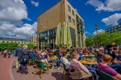 Amsterdam Nederländerna - Juli 10, 2015: Typisk det friagatarestaurang med folk som blöter i solen och dricka Arkivfoto