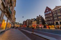 Amsterdam Nederländerna - Juli 10, 2015: Typisk holländsk charmig gata med hus för röd tegelsten på båda sidor Fotografering för Bildbyråer