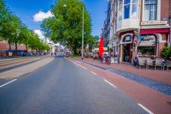Amsterdam Nederländerna - Juli 10, 2015: Typiska charmiga gator med traditionella holländska byggnader på båda sidor som är trevl Royaltyfri Fotografi