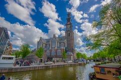 Amsterdam Nederländerna - Juli 10, 2015: Westerkerk kyrktar, härligt bygga tillsammans med vattenkanalen, distinkt torn på fotografering för bildbyråer