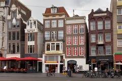AMSTERDAM NEDERLÄNDERNA - JUNI 25, 2017: Sikt till de gamla historiska byggnaderna på den Damrak gatan i Amsterdam Fotografering för Bildbyråer