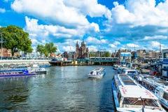 Amsterdam Nederländerna - Maj 28, 2015: invallning av kanalen i Amsterdam med turist- fartyg på en solig dag Arkivfoto