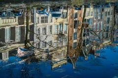 AMSTERDAM NEDERLÄNDERNA, MARS, 10 2018: Ursnygg sikt av att reflektera som bygger över den flodAmstel gränsmärket i gammal europé Royaltyfria Foton
