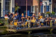 AMSTERDAM NEDERLÄNDERNA, MARS, 10 2018: Utomhus- sikt av oidentifierat folk i en restaurang som sitter och tycker om Arkivfoto